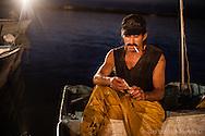 Pescador descansa en su panga después de entregar el producto obtenido durante la noche.