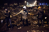 Anti-government protesters hastily reconstruct and reinforce barricades that were previously stormed by riot police near Maidan square in Kiev, 20 February 2014.