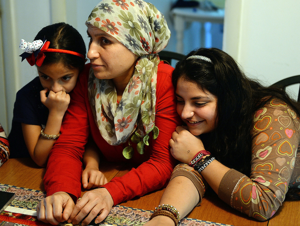 6/30/16 :: REGION :: LYNCH :: Fulla, 7, left, and Fidan, 17, right, lean in close to their mother Fahima Jemmo during discussions around the dining room table following English lessons Thursday, June 30, 2016 in their rented Ledyard home. Hasan Mahmoud and Fahima Jemmo and their children Fidan, 17, Hanif, 15 and Fulla, 7, are refugees from the conflict in Syria and lived for three years in Turkey before finally receiving approval to come to the United States. (Sean D. Elliot/The Day)
