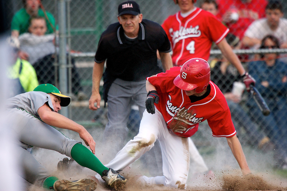 Lakeland High's Daniel Whitesitt falls to the ground after racing to home plate to make the tag on Jackson Olin from Sandpoint High during the Hawks 7-3 win Monday.