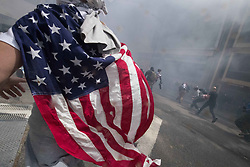 April 15, 2017 - Berkeley, California, U.S. - Trump supporters charge against anti-Trump protestors amid smoke from a smoke bomb on Center St. in Berkeley. Fist fights broke out among members of both groups on the streets around Martin Luther King Jr. Civic Center Park, where pro-Trump supporters had scheduled a rally. Fireworks and smoke bombs were thrown into the crowd, and a few demonstrators were doused with pepper spray. (Credit Image: © Paul Kuroda via ZUMA Wire)