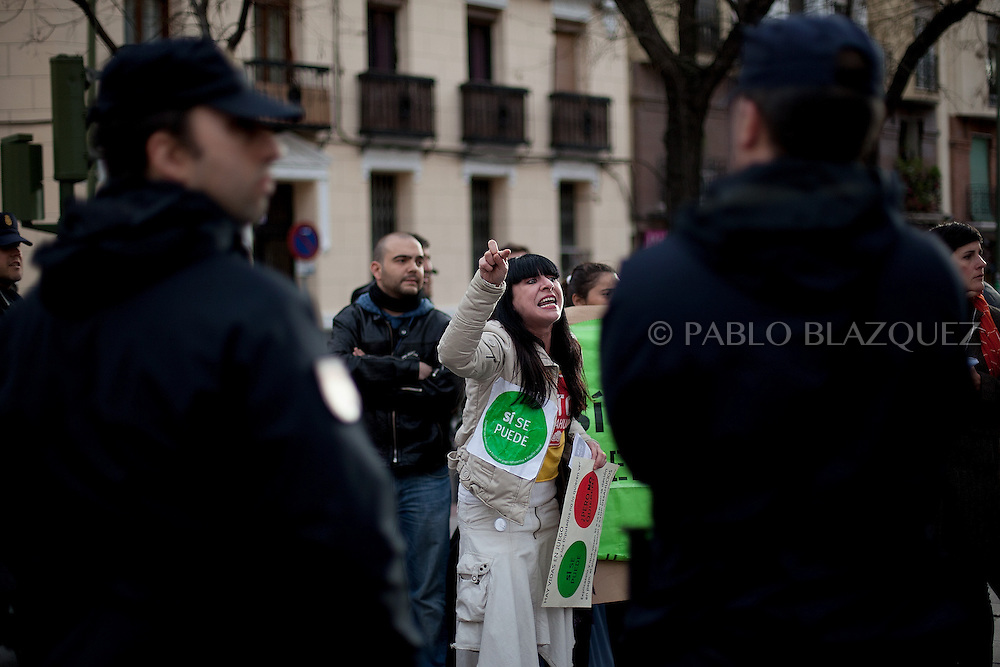 An Anti-eviction activists complain against police behavior after a 'escrache' outside the house of Popular Party Deputy Mari Luz Prieto, on April 4, 2013 in Madrid, Spain. Placard reads 'Yes we can, but they don't want'. The Mortgage Holders Platform (PAH) and other anti evictions organizations are organizing 'escraches' for several weeks under the slogan 'There are lifes at risk' to claim the vote for a Popular Legislative Initiative (ILP) to stop evictions, regulate dation in payment and social rent outside Popular Party deputies' houses and offices..'Escraches' are form of peaceful public protest that was used in Argentine in 1995 to point to pardoned genocides of Argentenia's Dictatorship within their neighborhoods.