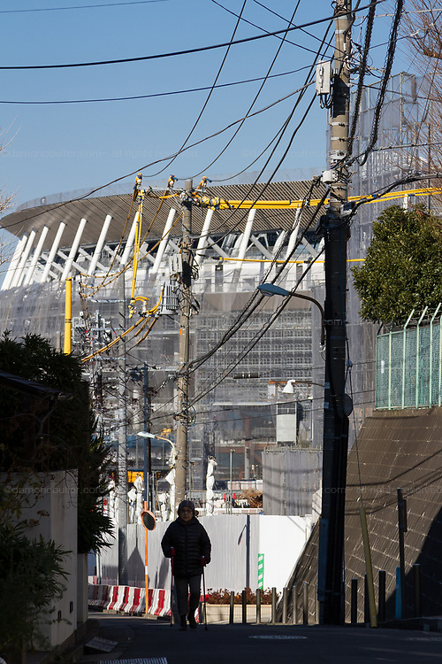 An older Japanese woman walks in a street with the construction of the main stadium for the 2020 Tokyo Olympics behind. Gaiemmae, Tokyo, Japan. Saturday January 5th 2019.