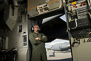 A U.S. Air Force loadmaster stands in the troop door that overlooks the flightline...Air Force aircraft transport most of the supplies and military equipment to the combat zone. Specialists must weigh, sort and load all of the gear before it heads to its location abroad. Air Force loadmasters and pilots ensure the safe transport of all equipment required in the field.
