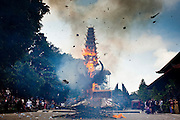Apr. 25 -- UBUD, BALI, INDONESIA:   The funeral pyre for Cokorde Gede Raka, a member of Ubud's royal family, is set alight Sunday, Apr. 25. Balinese are Hindus and cremate their dead. Balinese funerals are elaborate - and expensive - affairs. A funeral for one person costs a minimum of 45 million rupiah (about $5,000 US). The body is placed into the bull's body at the cremation and cremated in the bull. The funeral pyre is burnt adjacent to the bull. That is what a family may earn in two to three years. The result is that only the rich can afford formal cremations. The body (in the casket) is placed in the top of the funeral pyre and the procession takes the body to the cremation site. The funeral pyre, and the body, are spun at intersections to confuse the spirits so the soul doesn't try to return to its home and to confuse evil spirits.    PHOTO BY JACK KURTZ