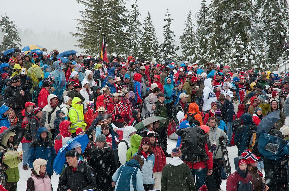 Crowds cheer and wave flags for the biathlon competition on a snowy winter day during the 2010 Olympic Winter Games in Whistler, BC Canada.