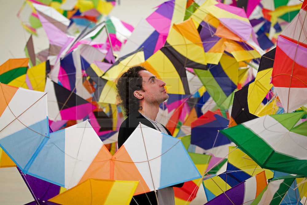 © Licensed to London News Pictures. 17/06/2013. London, UK. A Saatchi Gallery employee views 'Planos-pipas n17' (2013) an intricate kite style paper sculpture by Brazilian artist Marcelo Jacome at the press view for a new exhibition taking place at the West London based gallery. The exhibition, which runs from the 18th of June to the 29th of September 2013 at the Saatchi Gallery, is entitled 'Paper' and aims to challenge the viewers perceived ideas and expectations of the material in a world where its use is becoming rare thanks to emails and the internet  Photo credit: Matt Cetti-Roberts/LNP