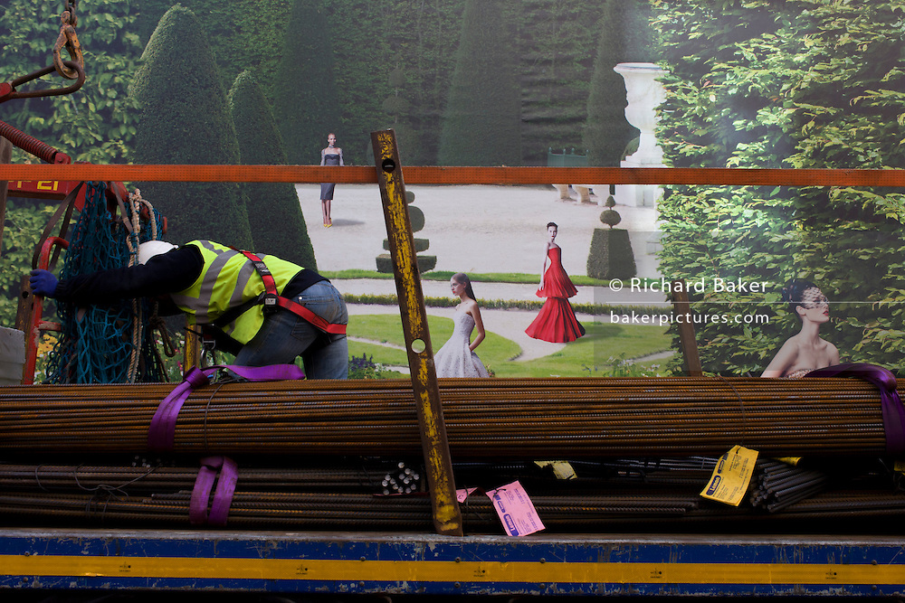With a background of hanging hoarding media, workman organises delivery of construction materials on the back of a lorry, to a Dior shop being refurbished in central London.
