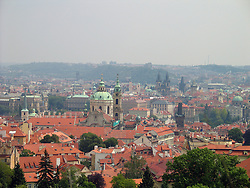 Aerial view of the dome and tower of St Nicolas Cathedral, surrounded by red roofs, Prague, Bohemia, Czech Republic