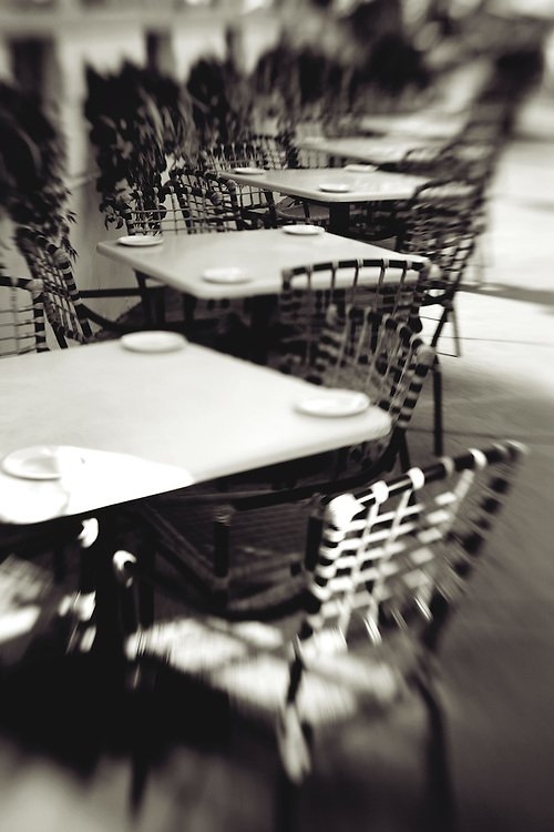outdoor cafe tables empty,vertcle black and white