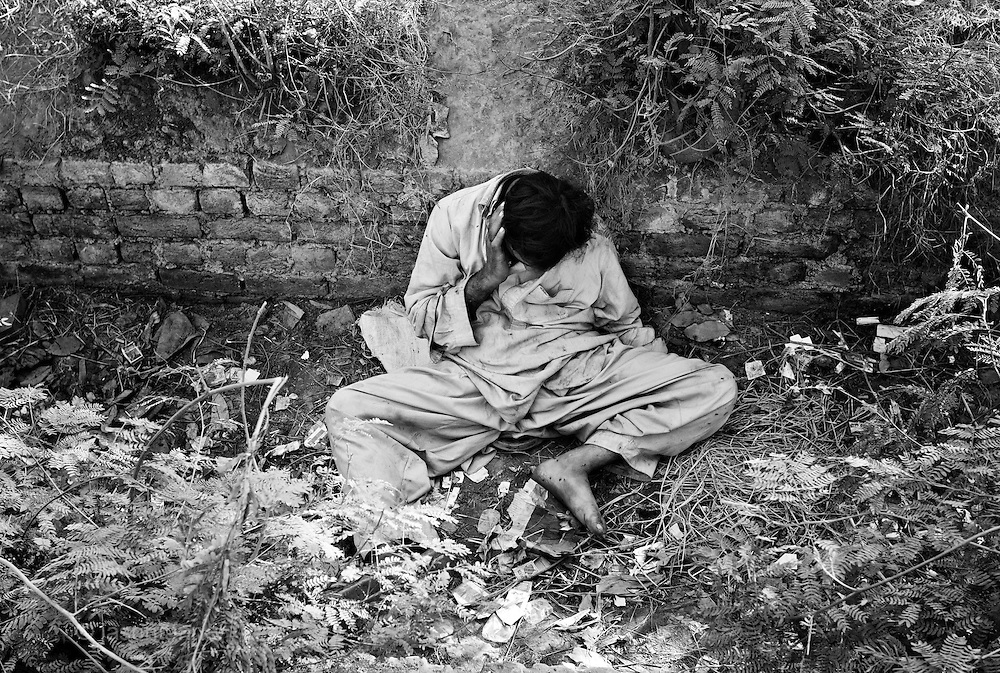 A heroin addict lies comatose in the drainage gutter alongside the main highway leading to Islamabad from Peshawar....Record opium crops in neighbouring Afghanistan have resulted in a cheap, affordable and plentiful supply of heroin and opium in Pakistan...In the frontier town of Peshawar, a gram of heroin sells for 100 rupees, little more than a dollar. Most addicts smoke or ?chase the dragon?, some inject but the inaccessibility of syringes dictate most addicts smoke the drug...Opium can be found in its pure form, fresh from record harvests in Afghanistan. Most is processed into heroin in the many factories along the Afghan / Pakistan borer, but some is retained, especially in the tribal province, for ?traditional medicinal? purposes such as bile din tea for curing arthritis and flu symptoms...Along the Peshawar ? Islamabad road addicts prepare heroin for smoking and injecting in full view of passers by on one of the countries busiest roads..