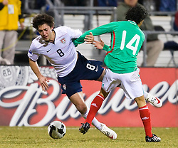 United States forward Clint Dempsey (8) is tackled by Mexico midfielder Israel Martinez (14).  The United States men's soccer team defeated the Mexican national team 2-0 in CONCACAF final group qualifying for the 2010 World Cup at Columbus Crew Stadium in Columbus, Ohio on February 11, 2009.