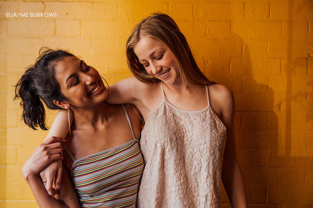 Teen friends smiling in front of yellow brick wall.