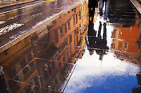 Reflection off a couple walking on a slate sidewalk in Rome Italy. -via del babuino