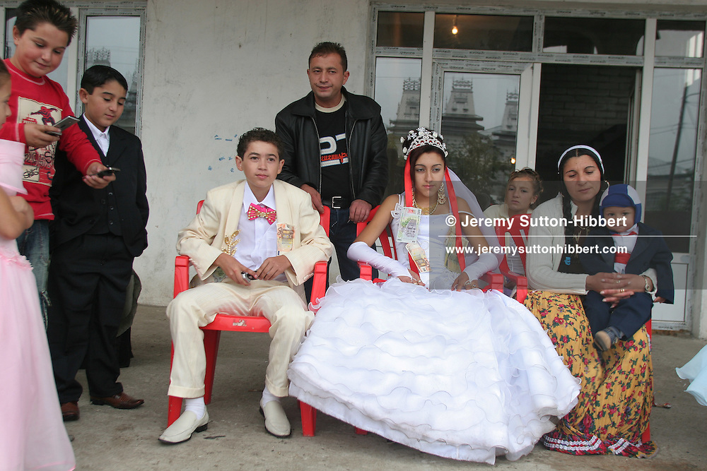 A young married roma (gypsy) couple sit with the bride's parents, in Sintesti, Romania, on Saturday, Sept. 23rd 2006. The wedding between Garoafa Mihai, aged 14, and Florin 'Ciprian' Lulu, aged 13, Roma (gypsies) from the village of Sintesti,15 kilometres from Bucharest, Romania. Their partnership was decided by their parents and not through love, and under Romanian law is illegal. The children will neither complete legal paperwork for the wedding, nor visit the local Romanian Orthodox church for a blessing. On her wedding day Garoafa wore approximately 30-40,000 USD of gold Franz Josef coins on her dress, part of the large dowry that she takes with her as she begins her married life. For the guests and for the people of the village another 30,000 USD of pigs were killed to be eaten and given away as presents of food. Another 30,000 USD was spent on famous Roma musicians to come and sing 'manele'  type music at the wedding extolling the wealth and status of their patrons for the weekend in their songs.