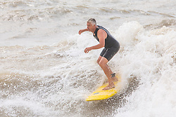 © Licensed to London News Pictures. 11/08/2019. Brighton, UK. Surfers take advantage of the strong waves to head out on to the sea in Brighton and Hove. Photo credit: Hugo Michiels/LNP