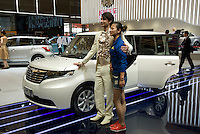 A Western model poses with a Chinese visitor on the Great Wall stand at Shanghai autoshow 2009