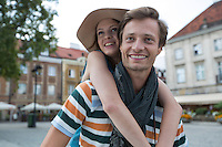 Happy man piggybacking woman on street during vacation