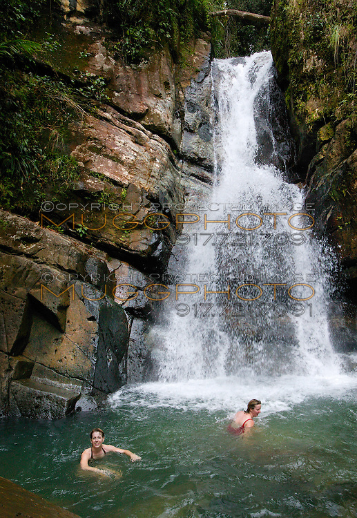 two women enjoy swimming in La Mina Falls in ElYunque Rainforest, Puerto Rico