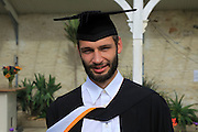 Portrait of male graduate wearing academic gown and mortarboard, graduation ceremony, University of Falmouth, Cornwall, England, UK - model released