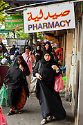 07 JULY 2011 - BANGKOK, THAILAND:   Women walk under a pharmacy sign in Arabic and English on Soi 3 in the Soi Arab section of Bangkok, Thailand. Soi Arab started as an alleyway in Bangkok (Soi is the Thai word for alley or small street). What started as an alley has now grown into a neighborhood that encompasses several blocks of restaurants, hotels and money exchanges that cater to Middle Eastern visitors to Thailand. The official name of the street is Sukhumvit Soi 3/1, located in North Nana between Sukhumvit Soi 3 and Sukhumvit Soi 5, not far from the Nana Plaza night-life area and the Grace Hotel popular among Arabs.    PHOTO BY JACK KURTZ