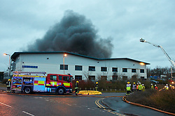 © Licensed to London News Pictures.  15/01/2014. NEWPORT PAGNELL, UK. Around 50 firefighter tackle a large warehouse fire in Newport Pagnell. The heat from the fire melted the sides of the building and the fire continues to burn hours after the alarm was raised. The 100m by 80m warehouse is operated by Liebherr and is used to distribute cooling equipment. Photo credit: Cliff Hide/LNP