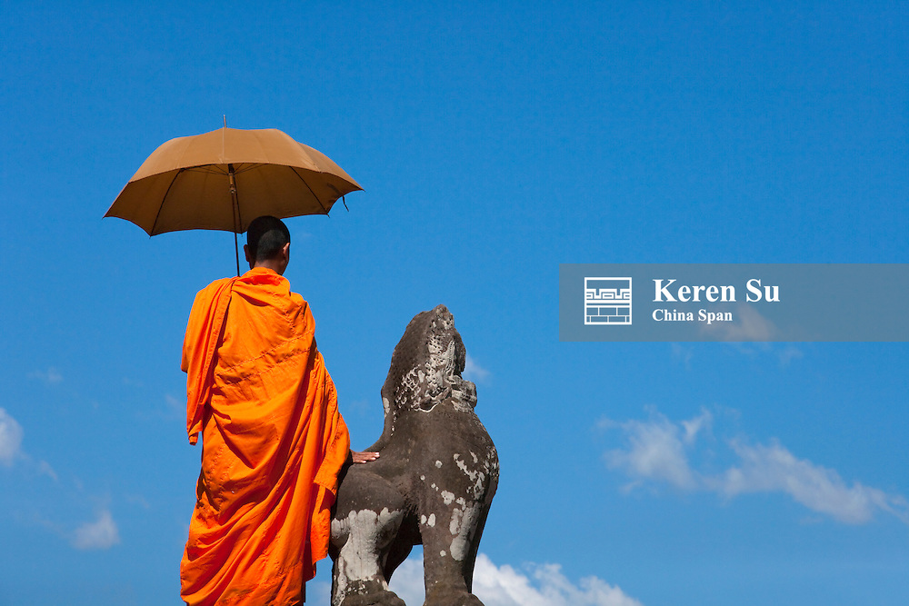 Monk with lion statue, Angkor Wat, UNESCO World Heritage site.