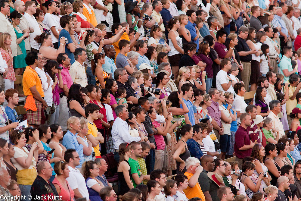 13 MAY 2009 -- TEMPE, AZ: People sing the Star Spangled Banner at the ASU graduation. President Barack Obama addressed the Arizona State University class of 2009 during the commencement program in Sun Devil Stadium in Tempe Wednesday evening.  PHOTO BY JACK KURTZ