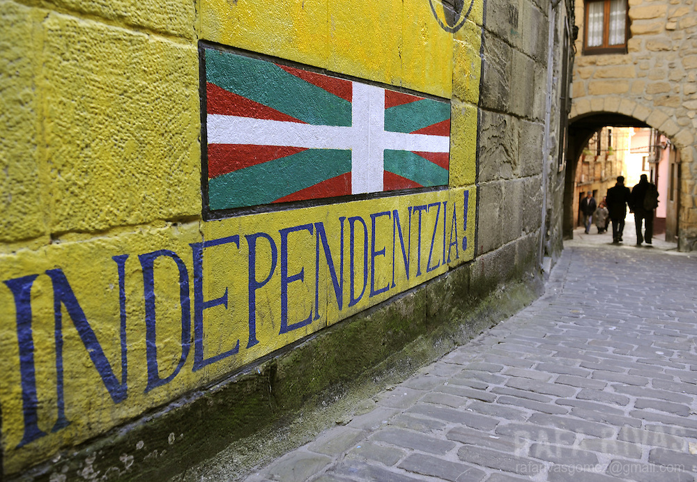 Some people walk past a pro independence mural painting in the northern Spanish Basque village of Pasajes de San Pedro, on February 18, 2009.