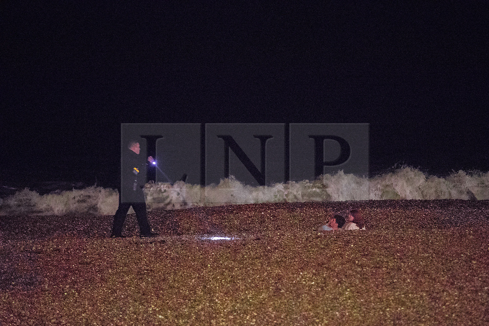 © Licensed to London News Pictures . 26/09/2017. Brighton, UK. A nightclub security man checks on the welfare of people on the beach . Revellers at the end of a night out in Brighton during Freshers week , when university students traditionally enjoy the bars and clubs during their first nights out in a new city . Photo credit: Joel Goodman/LNP