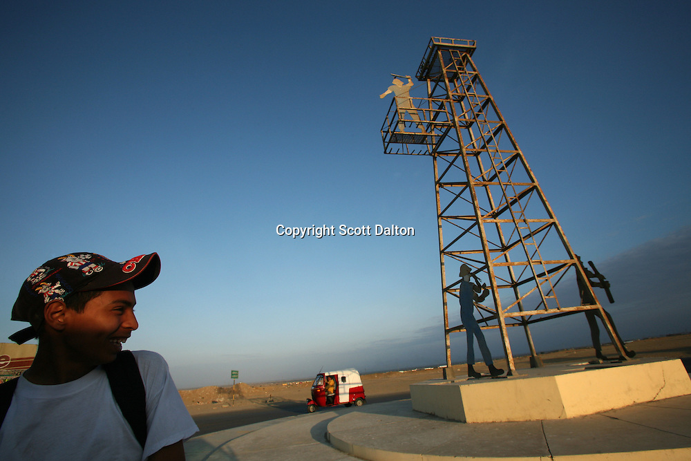 A boy looks on as a motorbike taxi driver rides by a monument to the oil industry in Talara on November 9, 2007. Talara, located on Peru's northern coast, is Peru's main oil producing region and the Chinese company SAPET has an oil field in the region. (Photo/Scott Dalton)