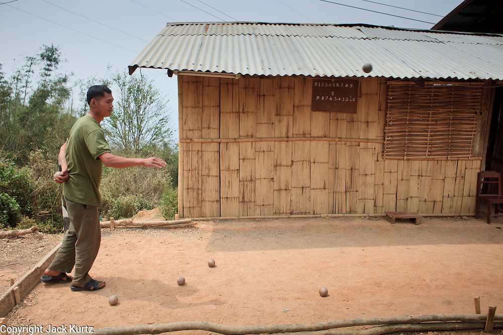 Mar. 16, 2009 -- LUANG PRABANG, LAOS: Men play bocce ball in a village on Highway 13 south of Luang Prabang, Laos. Highway 13 is the main highway in Laos and carries tourist and truck traffic between the capital Vientiane and Luang Prabang. The French brought bocce ball to Laos when the colonized the country. Fifty five years after the French left it's still popular in the mountains around Luang Prabang. Photo by Jack Kurtz