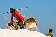 Man deposits farmed salt from traditional shoulder baskets, Bangkok, Thailand