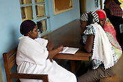 A nurse talks to patients wait outside Kasangati Health Centre in Uganda.