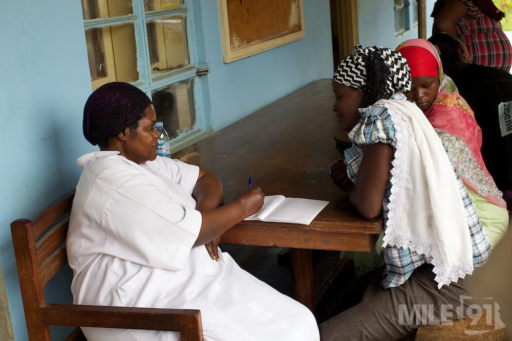 A nurse talks to patients wait outside Kasangati Health Centre in Uganda.