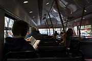 With the brightness of overhead lighting, a bus passenger reads a book on the top deck of a Routemaster bus in central London, on 4th December 2017, in London England.