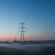 Electricity Pylons in early morning mist just outside of the village of Gordon in the Scottish Borders