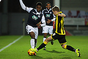 Millwall FC midfielder Fred Onyedinma and Burton Albion defender Damien McCrory challenge for the ball during the Sky Bet League 1 match between Burton Albion and Millwall at the Pirelli Stadium, Burton upon Trent, England on 1 December 2015. Photo by Aaron Lupton.