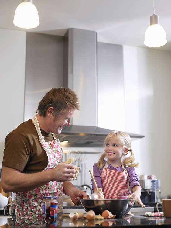 Girl (3-4) and father baking in kitchen
