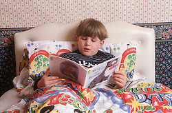 Young boy reading story book in bed,