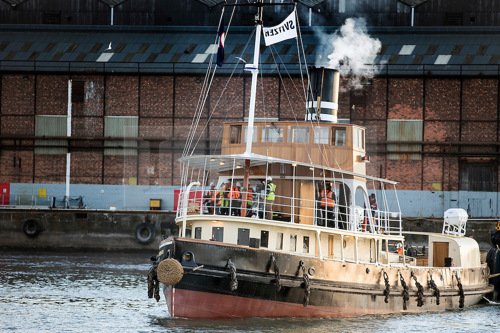 "© Licensed to London News Pictures. 04/05/2016. Birkenhead UK. Picture shows the Daniel Adamson leaving the Camel Laird ship yard in Birkenhead & making it's first public appearance for 30 years traveling across the Mersey last night to Canning Dock in Liverpool. The Daniel Adamson steam boat has been bought back to operational service after a £5M restoration. The coal fired steam tug is the last surviving steam powered tug built on the Mersey and is believed to be the oldest operational Mersey built ship in the world. The ""Danny"" (originally named the Ralph Brocklebank) was built at Camel Laird ship yard in Birkenhead & launched in 1903. She worked the canal's & carried passengers across the Mersey & during WW1 had a stint working for the Royal Navy in Liverpool. The ""Danny"" was refitted in the 30's in an art deco style. Withdrawn from service in 1984 by 2014 she was due for scrapping until Mersey tug skipper Dan Cross bought her for £1 and the campaign to save her was underway. Photo credit: Andrew McCaren/LNP ** More information available here http://tinyurl.com/jsucxaq **"