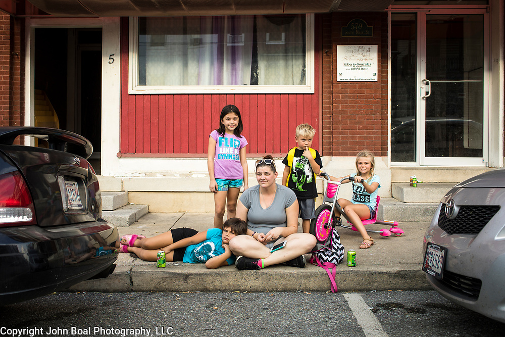 Desarae Mann, 7, rests her head on her mom, April's leg, next to her sister, Ariana Mann, 8, left. Also with the Manns are Siblings, Kam'ryn, 5, and Kaliyah Stouffer, 8 in downtown Smithsburg, Maryland, on Tuesday, September 26, 2017. Smithsburg is a very different town than the southern part of the district that includes Potomac and Germantown. Originally a District that was mostly rural, but included big towns like Frederick Hagerstown, along with smaller ones like Smithsburg, Maryland's 6th District was redistricted in 2011, combining rural northern Maryland regions with more affluent communities like near Washington D.C. turning the district from Republican to Democrat. <br />  <br /> CREDIT: John Boal for The Wall Street Journal<br /> GERRYMANDER