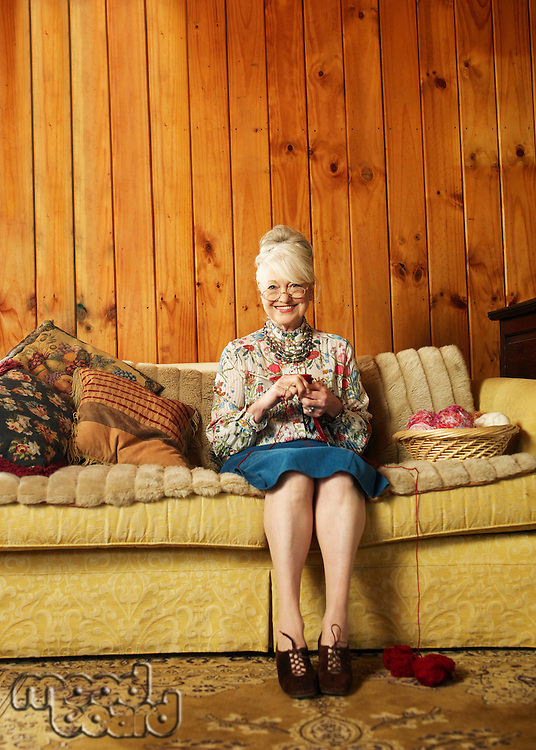 Portrait of happy senior woman knitting on sofa at home