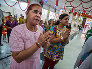 05 OCTOBER 2014 - GEORGE TOWN, PENANG, MALAYSIA:  Women pray in the Krishna temple before a procession honoring Durga in George Town during the Navratri procession. Navratri is a festival dedicated to the worship of the Hindu deity Durga, the most popular incarnation of Devi and one of the main forms of the Goddess Shakti in the Hindu pantheon. The word Navaratri means 'nine nights' in Sanskrit, nava meaning nine and ratri meaning nights. During these nine nights and ten days, nine forms of Shakti/Devi are worshiped.   PHOTO BY JACK KURTZ