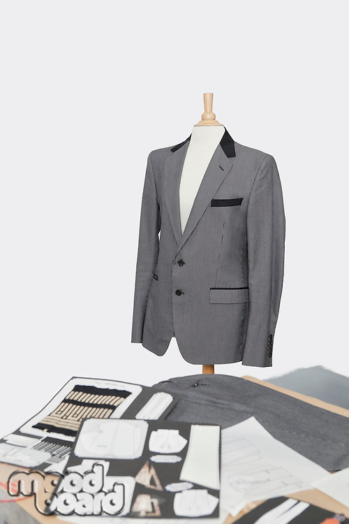 Suit on tailor's dummy with design layouts over gray background