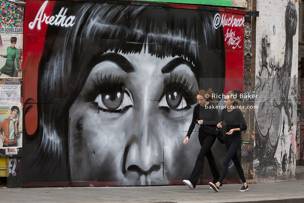 Londoners walk past a recent mural in Shoreditch (by artist Jules Muck) of Soul Queen Aretha Franklin who died a few days earlier, on 20th August 2018, in London, England.