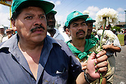 14 SEPTEMBER 2003 - CANCUN, QUINTANA ROO, MEXICO:  Rafael Allegria, a Honduran farm activist, and others carry flowers at a memorial service Sunday for Lee Kyung-hae, a Korean farm activist who publicly committed suicide Wednesday in Cancun to protest World Trade Organization agricultural policies, has been built where he died in a park in Cancun. Thousands of protestors opposed to the World Trade Organization and globalization have come to Cancun to protest the WTO meetings taking place in the hotel zone. Mexican police restricted most of the anti-globalization protestors to downtown Cancun, about five miles from the convention center.  PHOTO BY JACK KURTZ