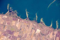 "While in orbit over the Brazilian coast, an astronaut aboard the International Space Station took this photograph of some of the country's famous coastal lagoons. This view shows a short 20-kilometer (12-mile) stretch of a lagoon shoreline where pointed sand spits jut into waters of Mangueira Lagoon (Lagoa Mangueira). The ends of the spits are under water, growing less visible with increasing depth.<br /> The space station crew had flown a similar orbital track a week earlier, taking panoramic shots like this one with Lagoa Mangueira on the lower right. They were likely in ""discovery mode,"" looking for features that might be worth tighter shots later in the Expedition.<br /> The spits and bays have a somewhat regular spacing, at least in geological terms. They are created as lagoon water slowly circulates while being driven by persistent sea breezes out of the east (top of the image). The water washes into the bays and then curves back out into the lagoon, carrying sand eroded from the shoreline. This sand is deposited in the tight, tan-colored lines we see as spits. The cells of circulating water tend to be the same size, depending on water depth, dominant wind strength, and the amount of sand available - translating into spits at roughly regular intervals. Regularly spaced spits form in many parts of the world, for instance along the coast of the Sea of Azov in southern Ukraine.<br /> Details in the photo suggest that strong winds from the north (left to right) have swept sand into thin tendrils on the south side of each spit. A single spit, whose origin is less clear, is also visible beneath the water surface of Lagoa Mangueira near the opposite side of the lagoon (top right).<br /> Astronaut photograph ISS043-E-101410 was acquired on April 10, 2015, with a Nikon D4 digital camera using an 800 millimeter lens, and is provided by the ISS Crew Earth Observations Facility and the Earth Science and Remote Sensing Unit, Johnson Space Center. The image was taken by a member of the Expedition"