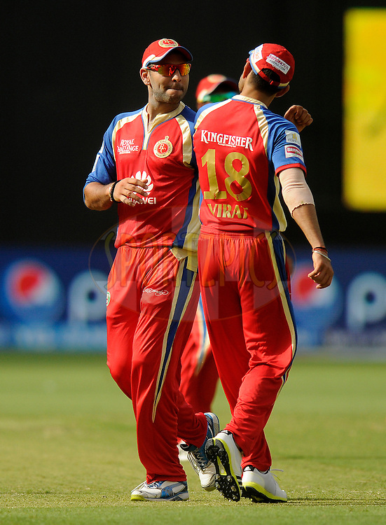Yuvraj Singh of the Royal Challengers Bangalore  and Virat Kohli captain of the Royal Challengers Bangalore celebrate the wicket of Lasith Malinga of the Mumbai Indians during match 5 of the Pepsi Indian Premier League Season 7 between the Royal Challengers Bangalore and the Mumbai Indians held at the Dubai International Cricket Stadium, Dubai, United Arab Emirates on the 19th April 2014<br /> <br /> Photo by Pal Pillai / IPL / SPORTZPICS