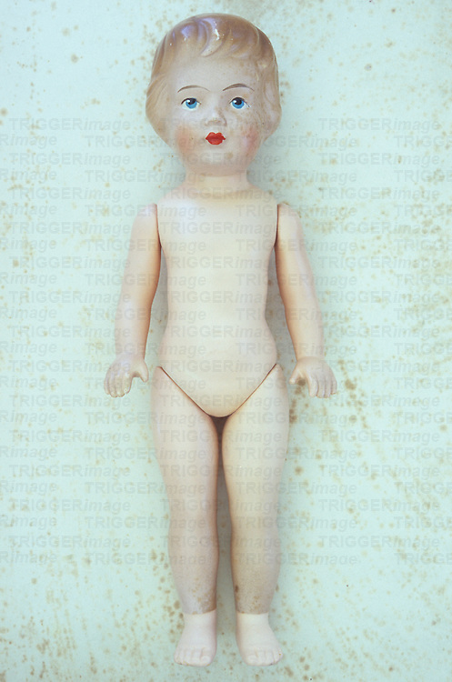Vintage female doll with face slightly freckled from ageing lying naked on antique paper